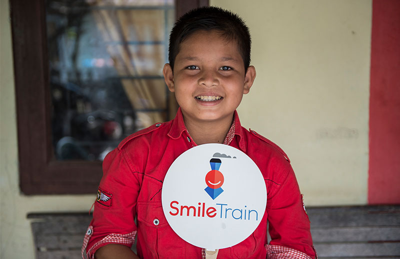 Deri holding Smile Train sign