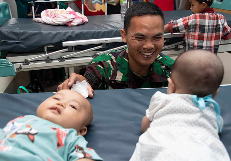 An Indonesian soldier smiles at two babies before their cleft surgeries