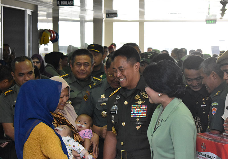An Indonesian general smiles at two babies after their cleft surgeries